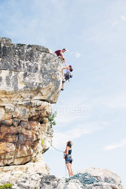 Distant view of climbers scaling steep rock face — Stock Photo