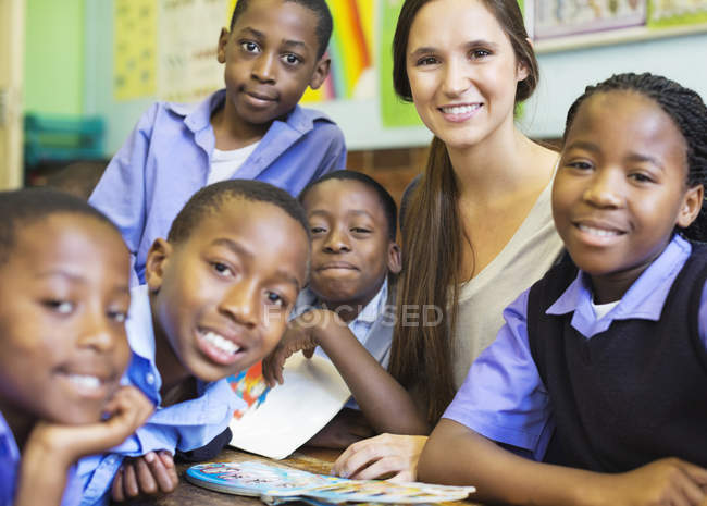 Teacher and african american students smiling in class — Stock Photo