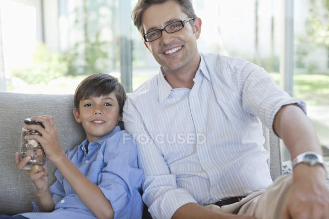 Father and son with change jar on sofa — Stock Photo