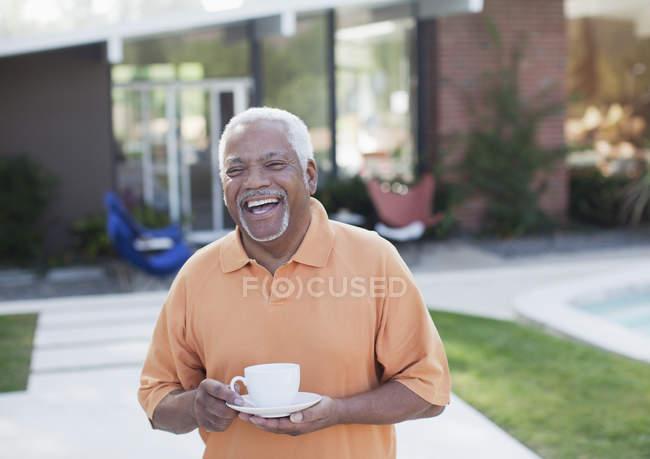Літня людина чашкою кави у дворі — стокове фото