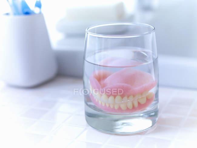 Primo piano delle protesi immerse in un bicchiere d'acqua — Foto stock