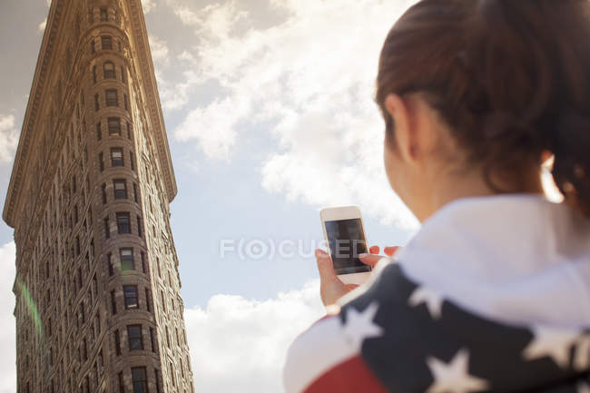 Woman taking picture of highrise — Stockfoto
