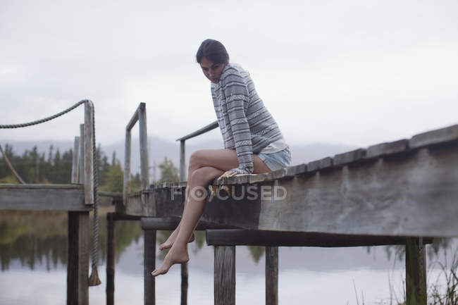 Serene woman sitting at edge of dock over lake — Stock Photo