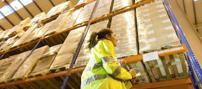 Travailleur écrivant sur le presse-papiers dans l'entrepôt — Photo de stock