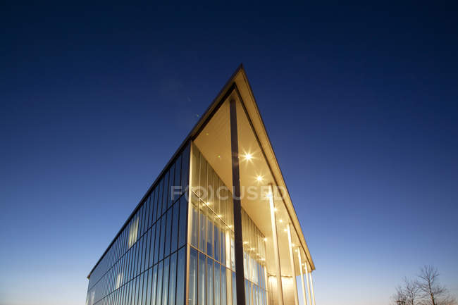 Modern building illuminated at dusk — Stock Photo