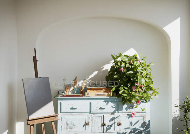 Easel with painting next to bureau with plants and supplies on patio — Stock Photo