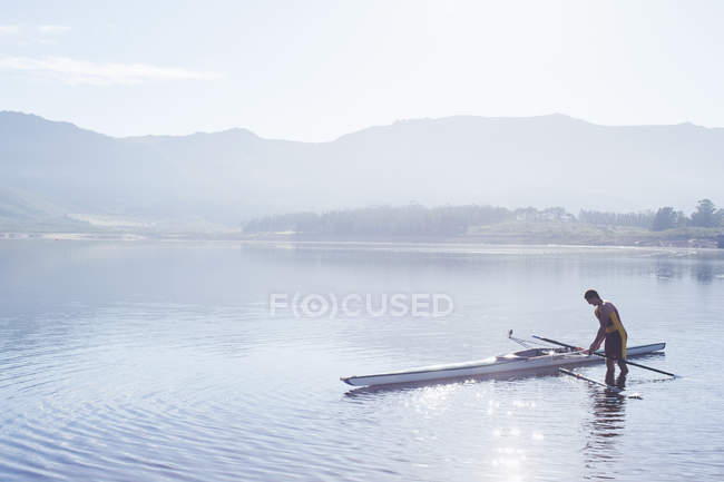 Hombre colocando remo en el lago - foto de stock