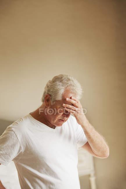 Старший мужчина держит голову в боль — стоковое фото