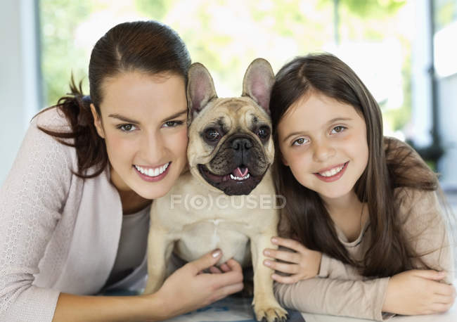 Усміхаючись, мати і дочка, обіймати собака — стокове фото