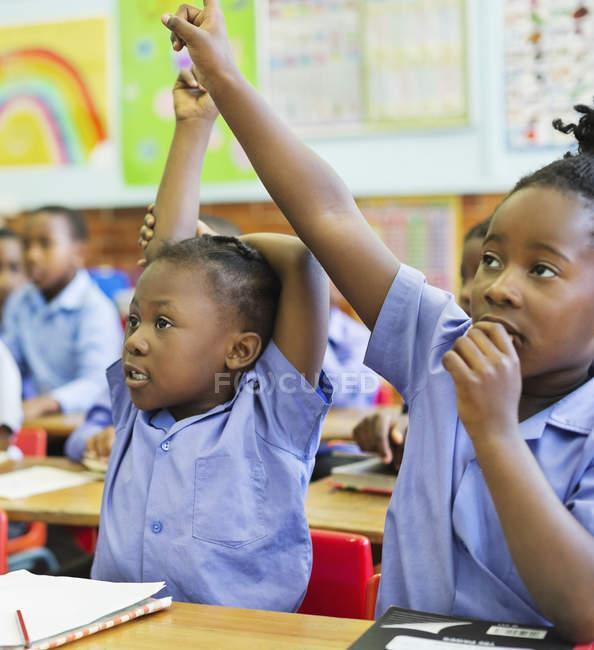 Studenti afro-americani alzando le mani in classe — Foto stock
