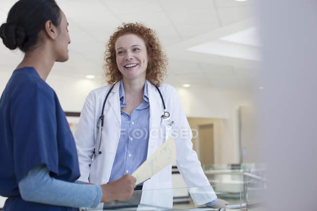 Médico y enfermera hablando en el pasillo del hospital - foto de stock