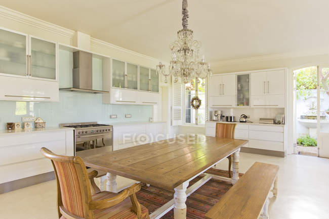 Chandelier over wooden table in kitchen — Stock Photo