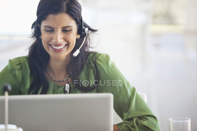 Businesswoman wearing headset at desk at modern office — Stock Photo