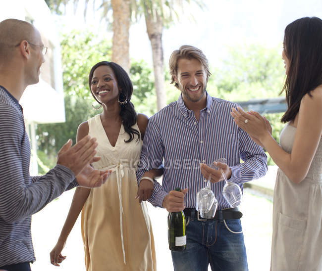 Young attractive Friends cheering smiling couple — Stock Photo