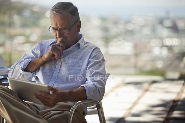 Літня людина, за допомогою планшетного комп'ютера на відкритому повітрі — стокове фото