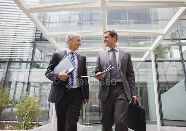 Des hommes d'affaires sortent ensemble de l'immeuble de bureaux — Photo de stock