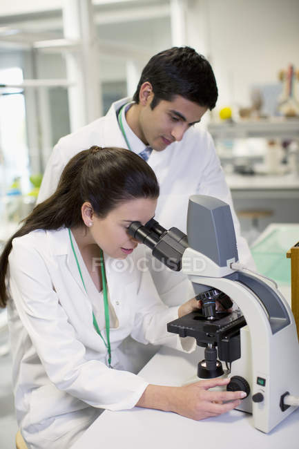 Scientists using microscope in laboratory — Stock Photo