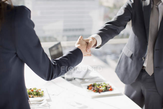 Businessman and businesswoman shaking hands at table with lunch — Stock Photo