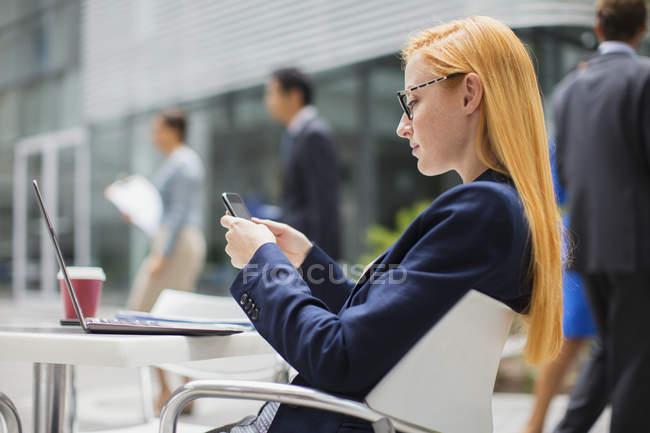 Empresária usando telefone celular na mesa do lado de fora — Fotografia de Stock