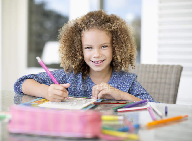 Portrait of curly girl coloring at table — Stock Photo
