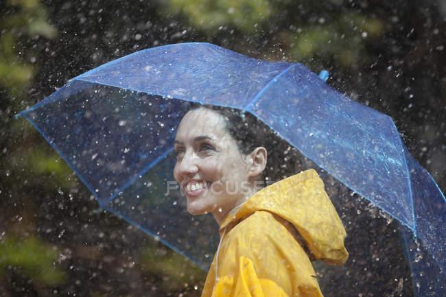 Mulher caucasiana feliz com guarda-chuva na chuva — Fotografia de Stock