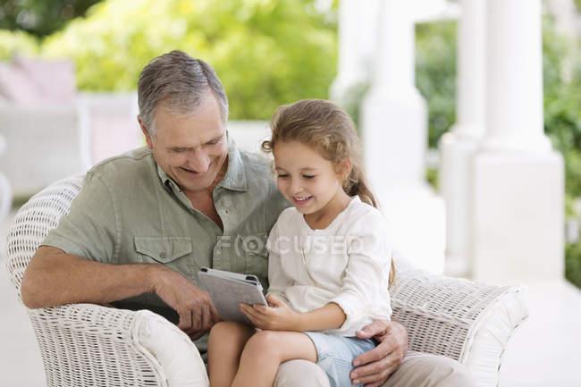 Homme plus âgé et petite-fille utilisant un ordinateur tablette — Photo de stock