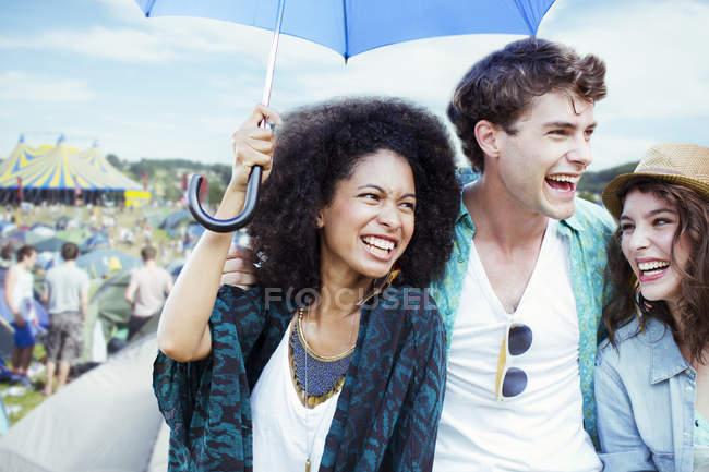 Друзья с зонтиком на музыкальном фестивале — стоковое фото