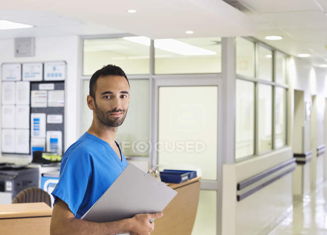 Enfermero, sonriendo en pasillo de hospital - foto de stock