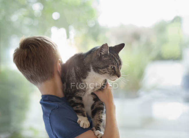 Rear view of caucasian boy holding cat — Stock Photo