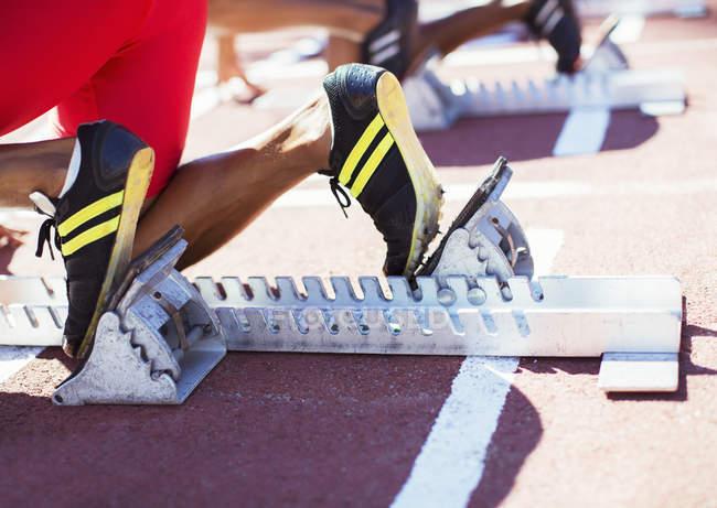 Ноги бегуна в стартовых блоках на пути — стоковое фото