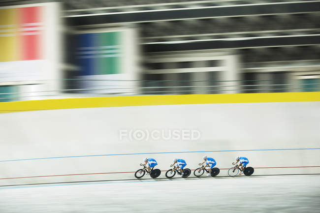 Track cycling team racing in velodrome — Stock Photo