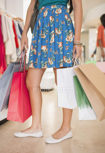 Woman carrying shopping bags in grocery store — Stock Photo