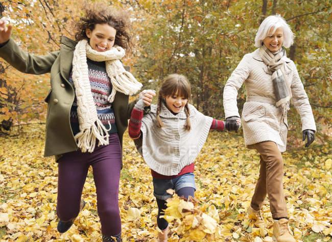 Tres generaciones de mujeres jugando en hojas de otoño - foto de stock