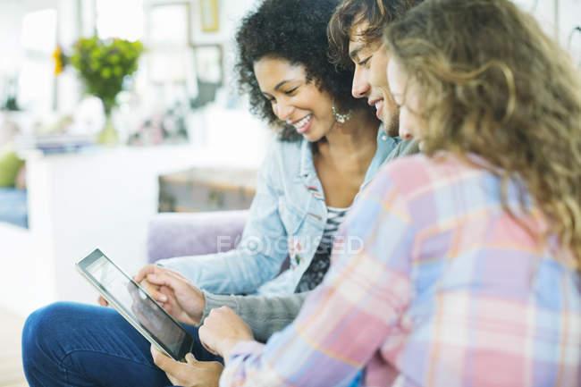 Друзі, використовуючи комп'ютер tablet на дивані — стокове фото