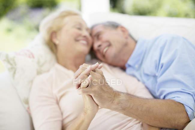 Старшие пары держатся за руки на диване — стоковое фото