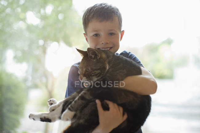 Smiling boy holding cat indoors at modern home — Stock Photo