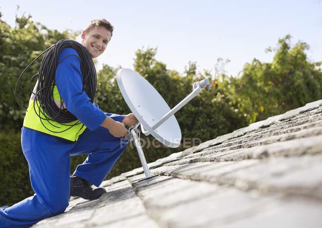 Рабочий устанавливает спутниковую тарелку на крыше — стоковое фото