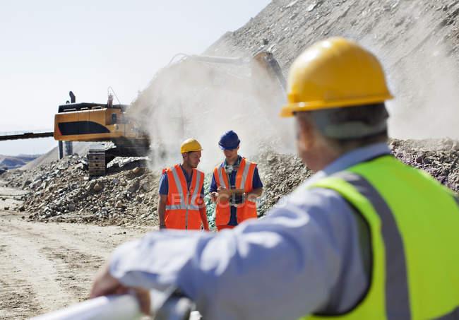 Geschäftsmann beobachten Arbeiter im Steinbruch — Stockfoto