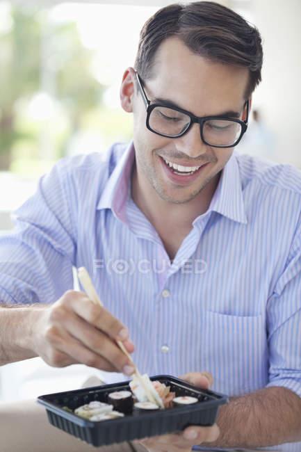Homme d'affaires mangeant des sushis au bureau moderne — Photo de stock