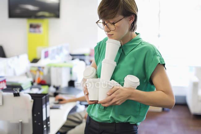 Geschäftsfrau Ausgleich leere Kaffeetassen im modernen Büro — Stockfoto