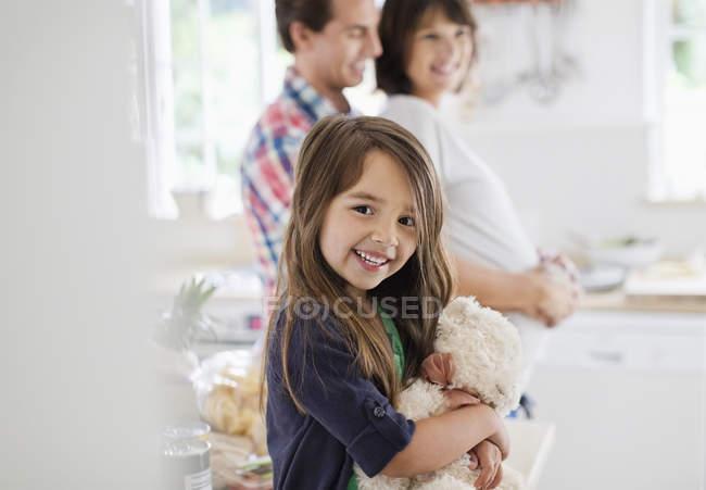Chica sosteniendo oso de peluche en la cocina - foto de stock
