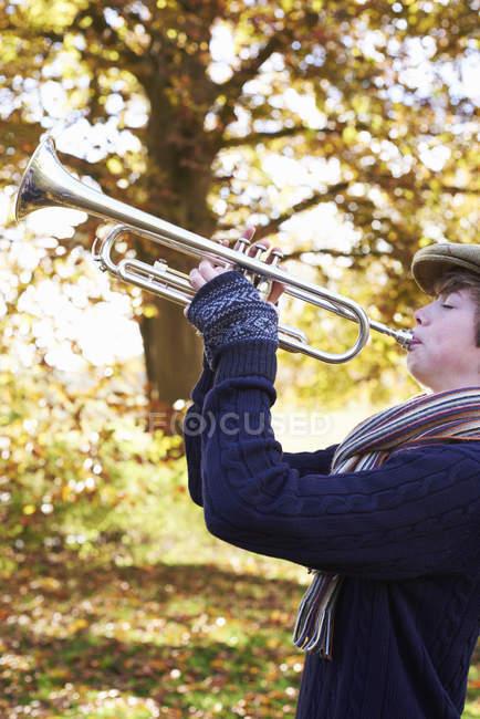 Teenage boy playing trumpet outdoors — Stock Photo
