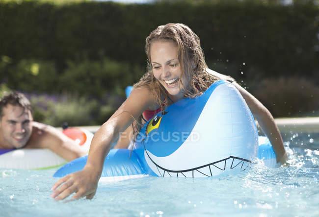 Mulher jogando no brinquedo inflável na piscina — Fotografia de Stock