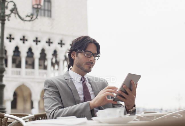 Uomo d'affari che utilizza tablet digitale al caffè sul marciapiede di Venezia — Foto stock