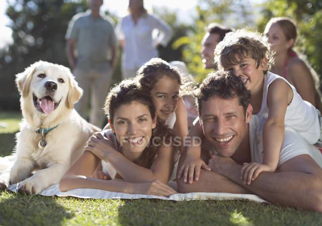 Щаслива родина розслаблюючим у дворі з собакою — стокове фото