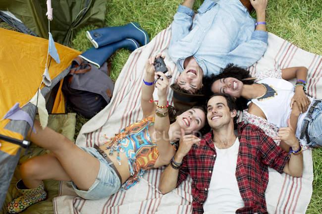 Amigos fazendo auto-retrato em cobertor fora da tenda no festival de música — Fotografia de Stock