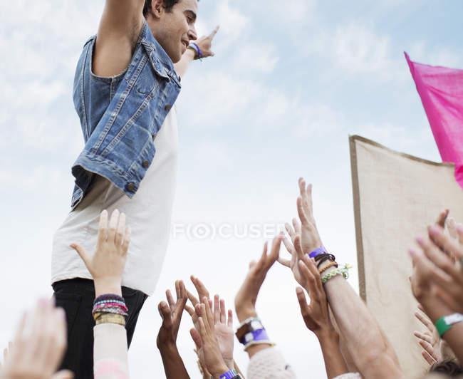 Исполнитель стоял выше ликующие толпы на фестивале музыки — стоковое фото