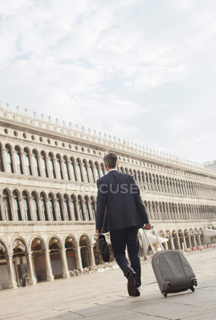 Businessman pulling suitcase through St. Mark's Square in Venice — Stock Photo