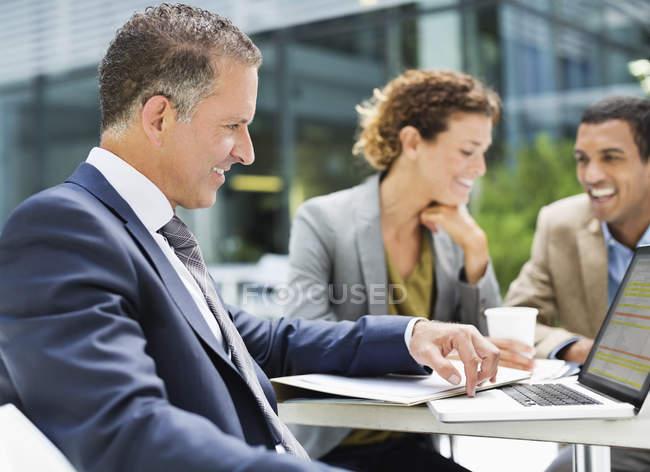 Les gens d'affaires parlent à l'extérieur du bureau moderne — Photo de stock