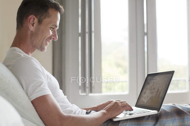 Smiling man using laptop in bed — Stock Photo